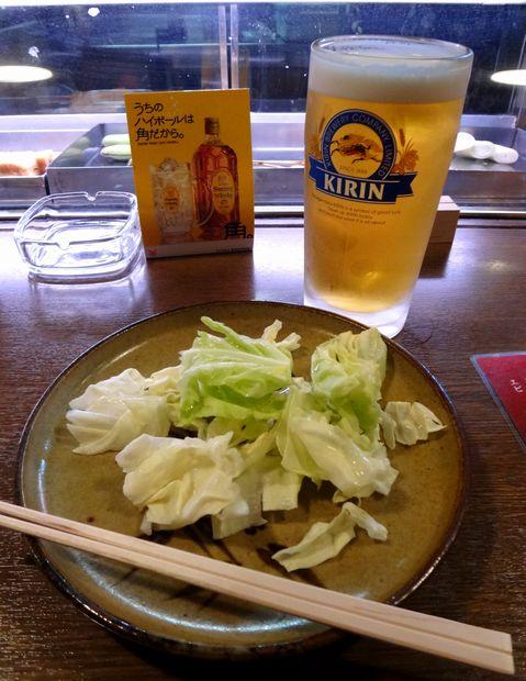 『屯所』生ビール中(550円)と、串物置き皿のキャベツ