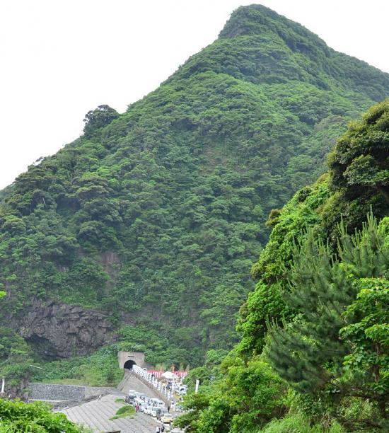 行者浜が尽きるところに 櫛の峰 がそそり立つ トンネルの左の海食崖に行者窟がある