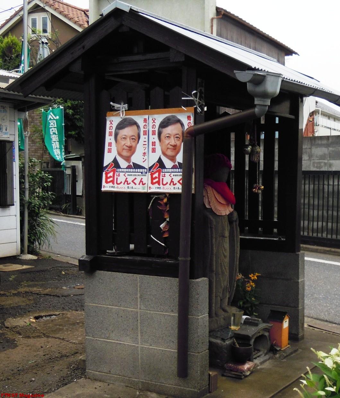 お地蔵さんに選挙ポスターを貼る白眞勲