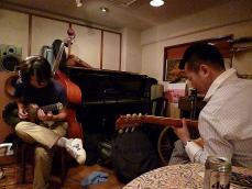 トラベルギターを弾くg馬場孝喜さんと馬場さんのギターを弾くお客様