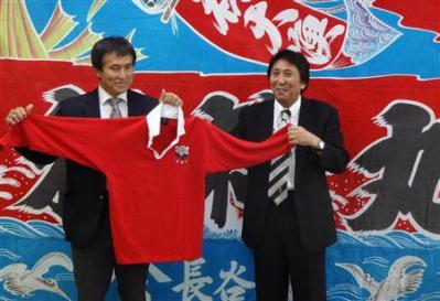 全盛期の国立競技場に舞った釜石応援用の大漁旗を前に、往年のジャージーを手にした松尾氏(右)と釜石OBの石山・スクラム釜石代表