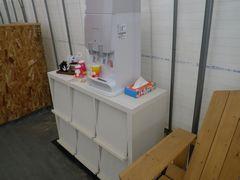[写真]受付ハウスに新たに設置したリビングボードとその上に乗せたウォーターサーバー