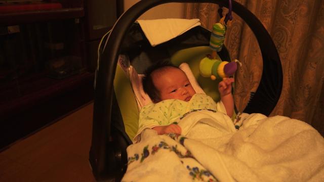 芋虫のおもちゃを押して音を楽しむ生後一か月の赤ちゃん